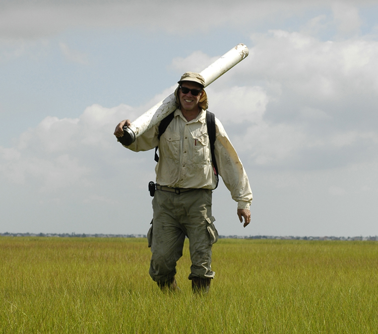 Velinsky standing in a salt marsh with a core barrel over his shoulder