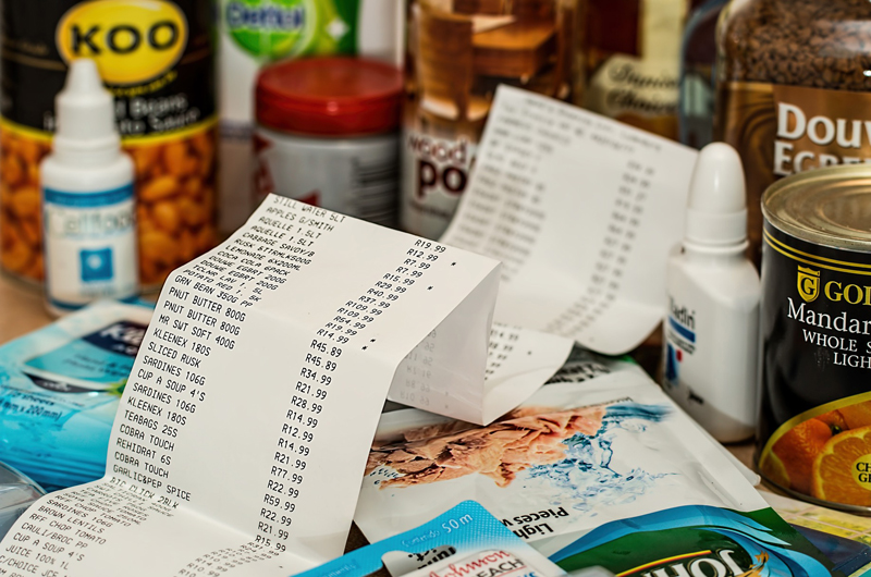 A receipt sitting on and near an assortment of groceries