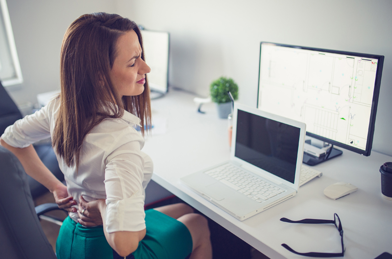 photo of a woman with back pain at an office desk