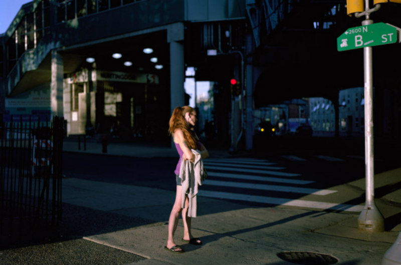 A woman stands on Kensington Ave. in one of photographer Jeffrey Stockbridge's portraits of a community struggling through the opioid epidemic. Stockbridge's work can be found at kensingtonblues.com.