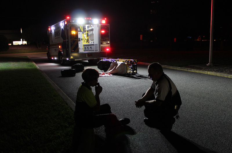 An EMT crouching in the dark with a patient outside an ambulance