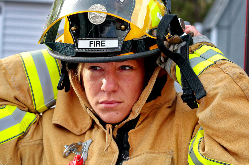 A woman firefighter putting on her helmet