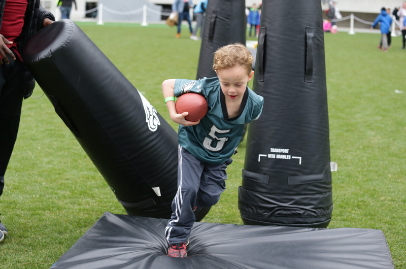 A boy in an Eagles jersey running through tackling dummies.