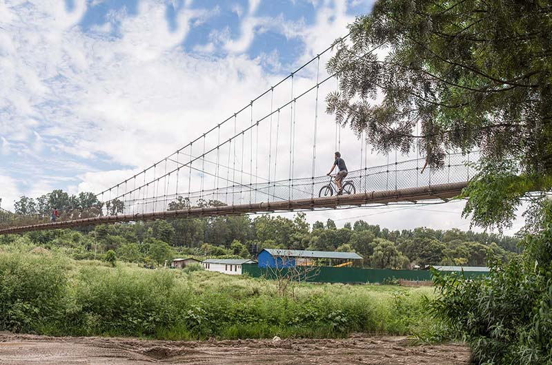 Joseph DiSalvo bikes across a bridge every day, with the bike he designed, on his way to Portal Bikes Workshop in Kathmandu, Nepal.