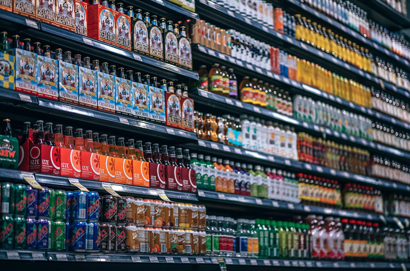 Full shelves with soda, fruit drinks and teas.
