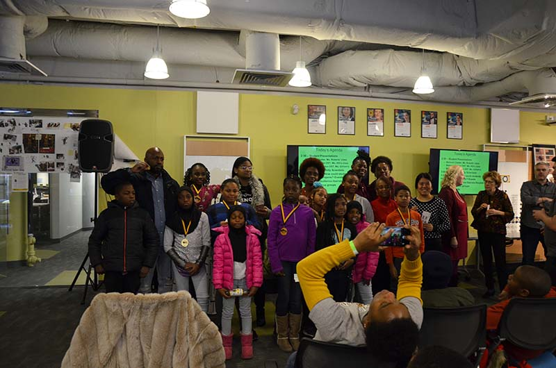 A group of students, teachers and family members pose for pictures at the Dec. 8 event at Drexel's ExCITe Center.