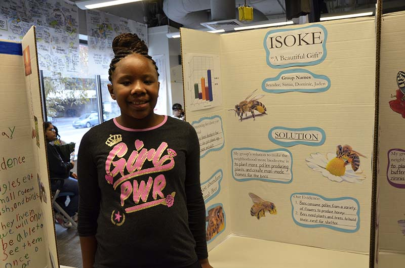 Sanaa Ward, a fourth-grade student at Belmont Charter, stands in front of the poster she helped create.