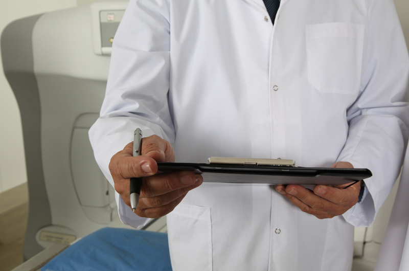 A shot of a doctor in a white coat holding a clipboard and a pen. His face is cut off from the frame.