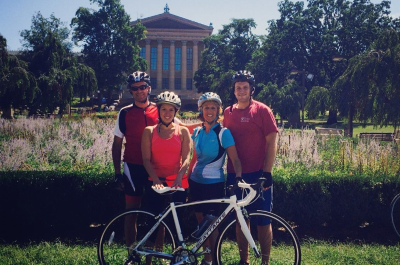 A family with a bike in biking clothes in front of the Philadelphia Museum of Art.