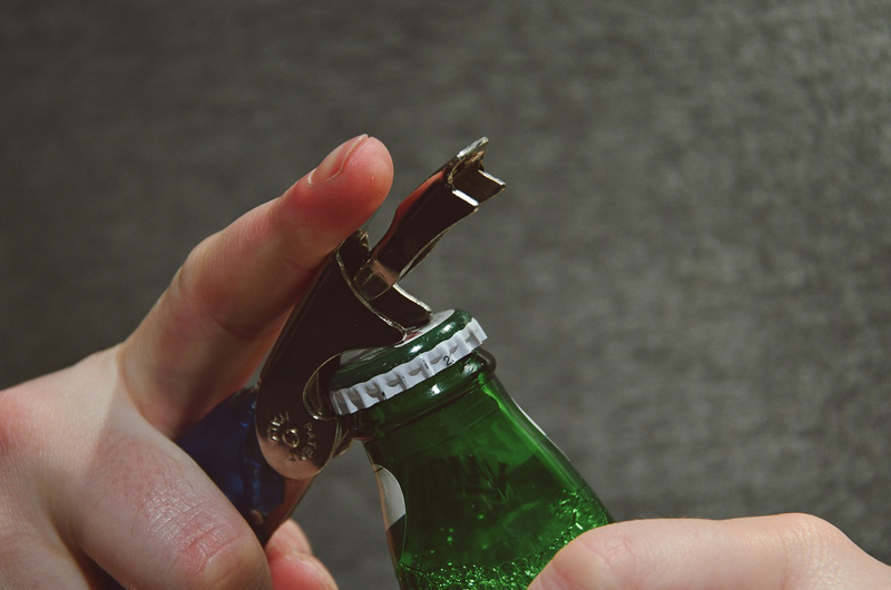 Hands opening a beer bottle