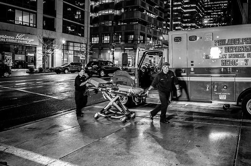 A pair of medics walking with a stretcher near their ambulance.