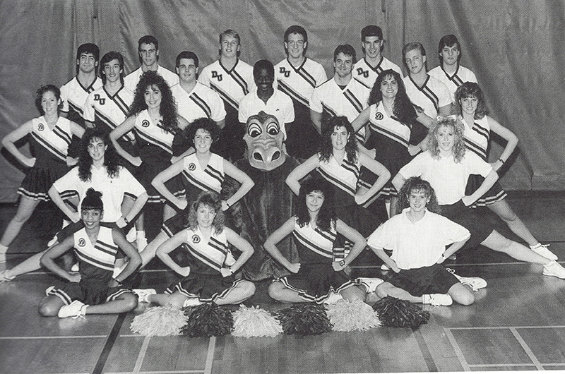 The Drexel Dragon posing with the University's cheer squad in the 1990 yearbook. Photo courtesy University Archives.