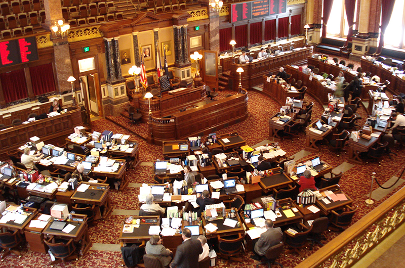 An elevated view of the Iowa State Senate with some people inside