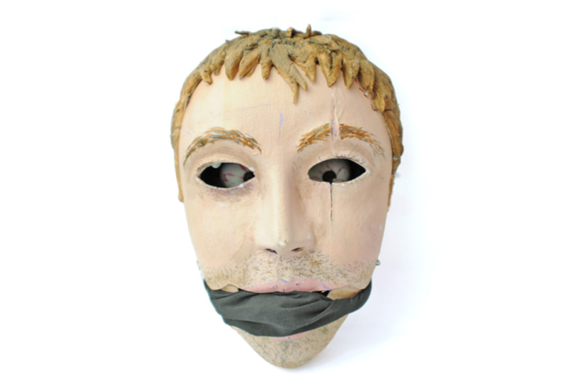 A mask depicting a face with a scar of an eye, with eyeballs deep within the eye holes and a gag over the mouth.