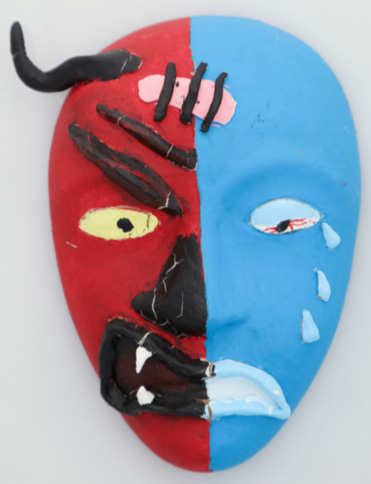 A mask that is split down the middle, with the left side seeming to depict a red, devil-like face and the right painted blue and showing a sad, human-like face with a band-aid between the two.