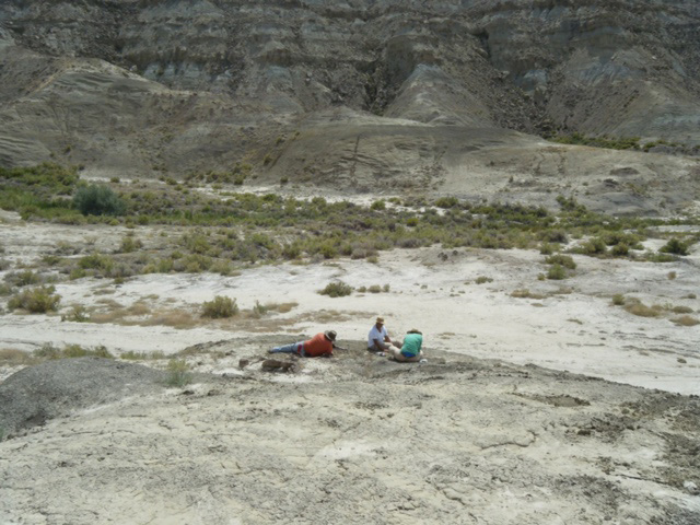 Three figures in the Montana Badlands digging.