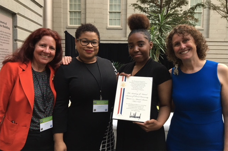 Four women involved with the WINS program gathered around their award certificate.