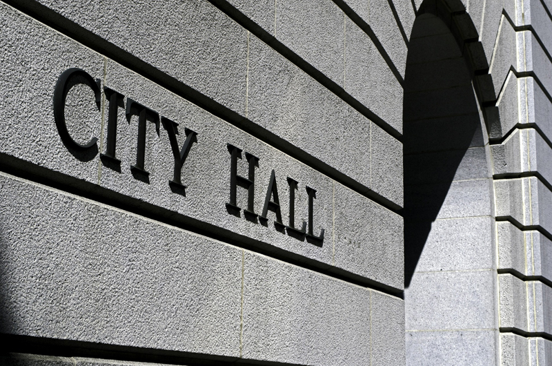 "The stone side of an entrance to a city hall building, with a ""City Hall"" sign."