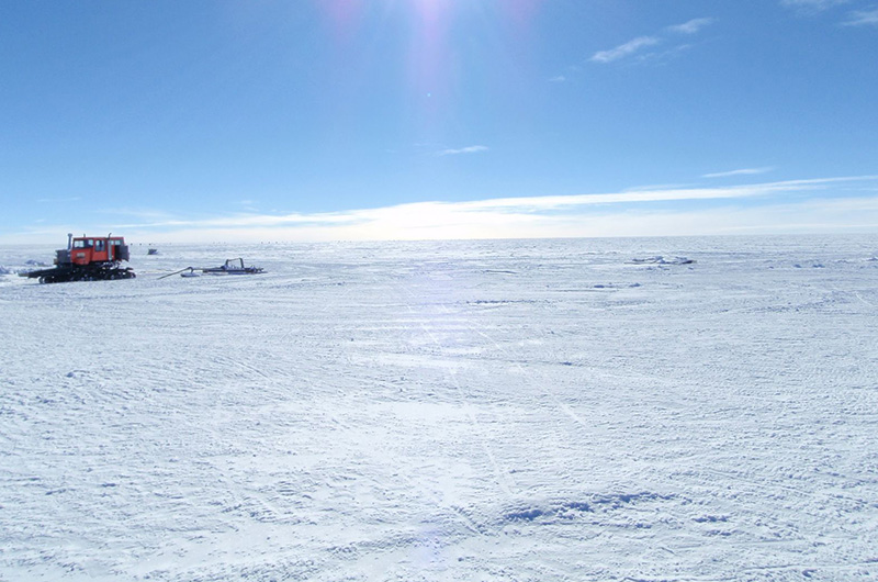 The East Antarctica landscape with a heavy tractor in the background