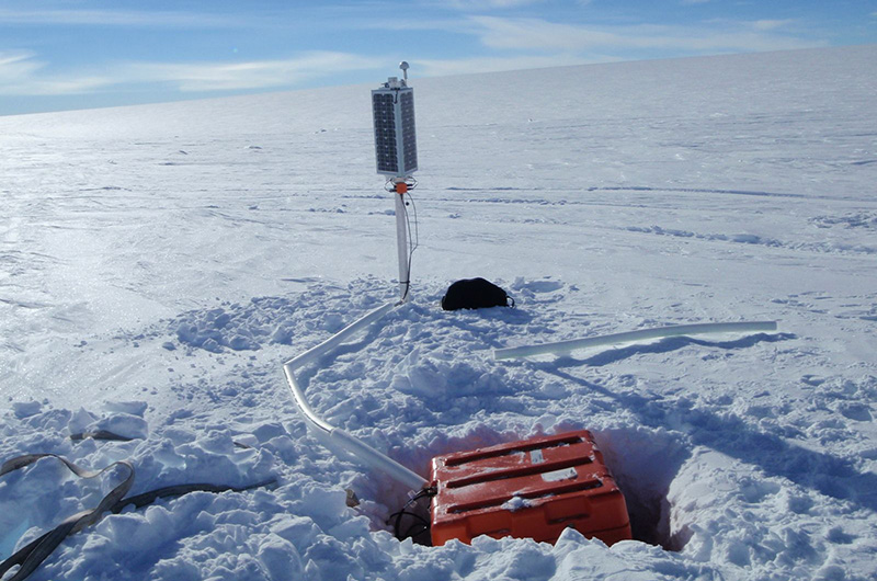 A sensor in an orange box buried in the vast Antarctica snow with a solar sensor on a post next to it