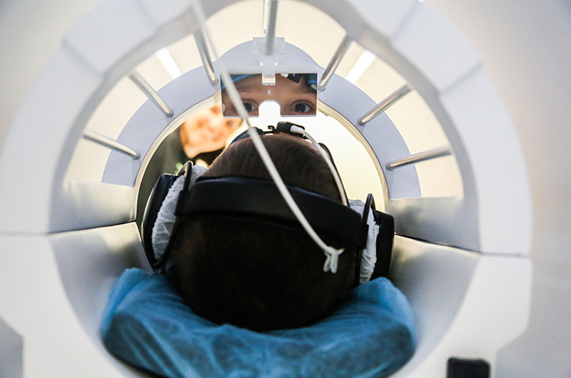 A person looking up at a mirror in an MRI machine