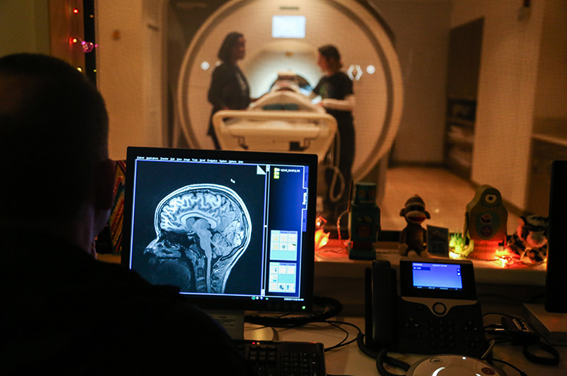 A person looking at a brain image on a monitor while someone else is helped into an MRI in the background.