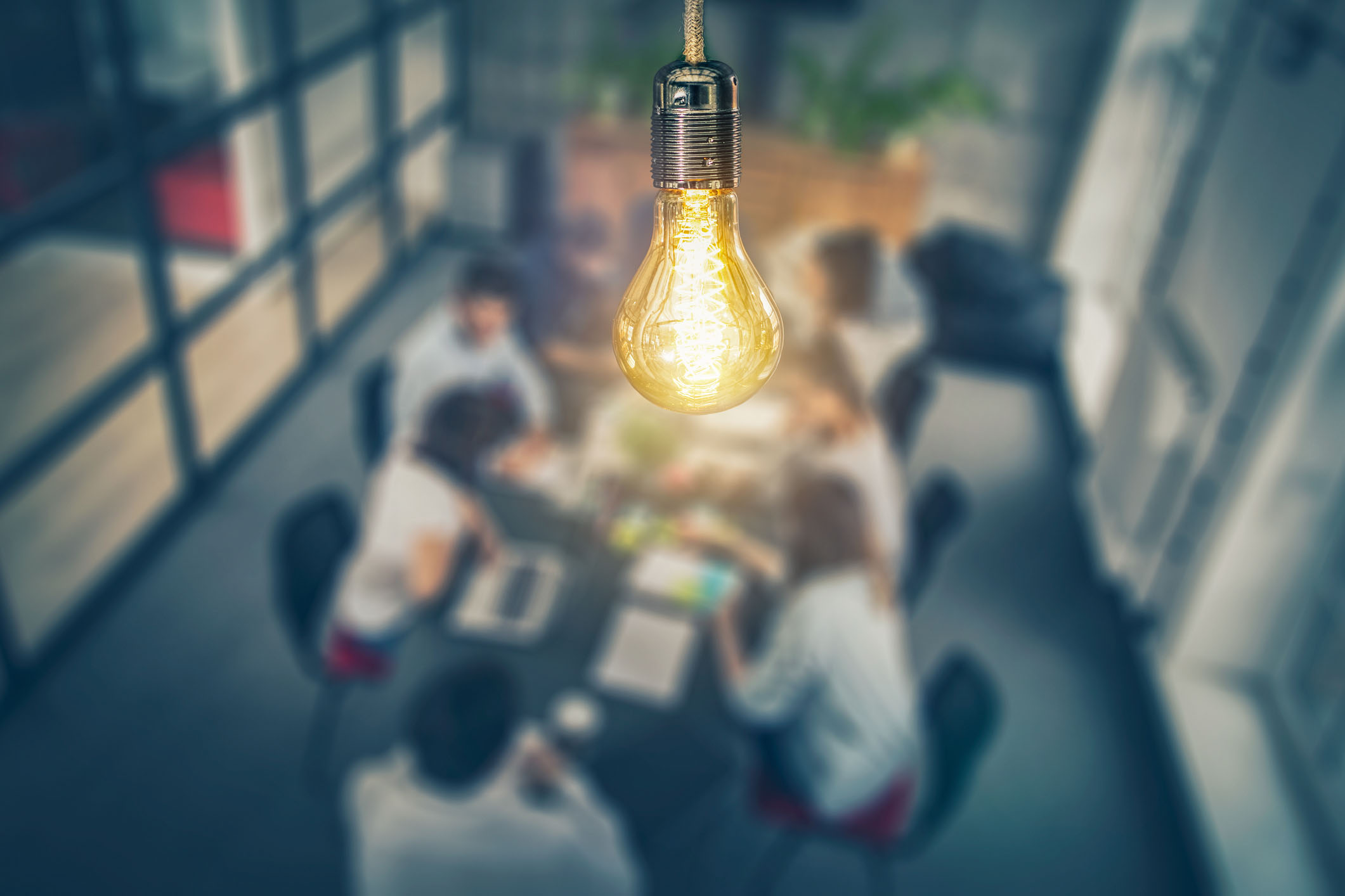 image of a lit bulb on top of a table at which entpreneurs are seated at