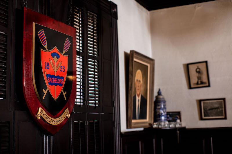 "The walls of the Button are filled with hanging memorabilia, like a plaque with the Bachelors Barge Club crest, left, and a painting of Olympic gold medalist and Bachelors Barge Club president W.E. Garrett Gilmore, or ""Loft,"" right."