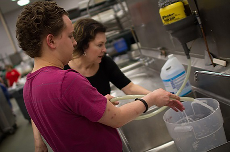 Woman helping young man fill bucket at sink