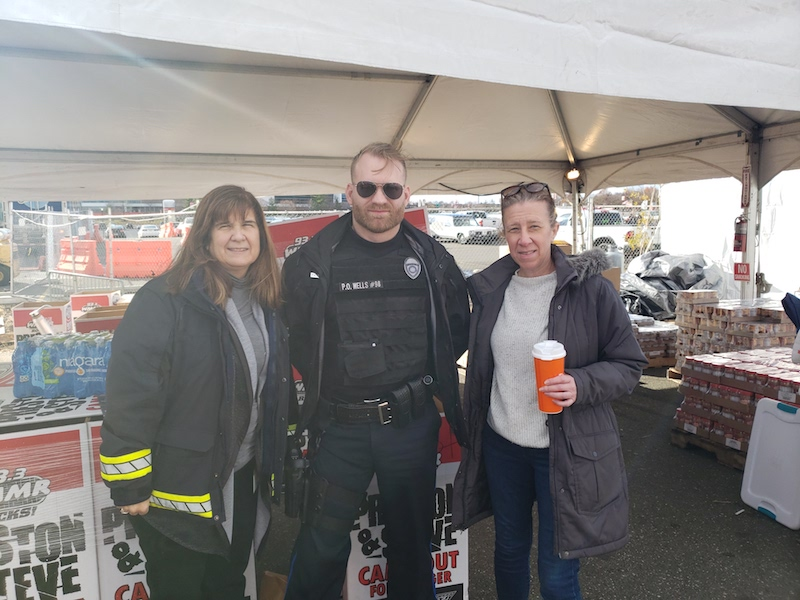 Drexel Public Safety's Madonna Calderoni, Police Officer Logan Wells, and Linda Moran drop off donations for Preston & Steve's Camp Out for Hunger.