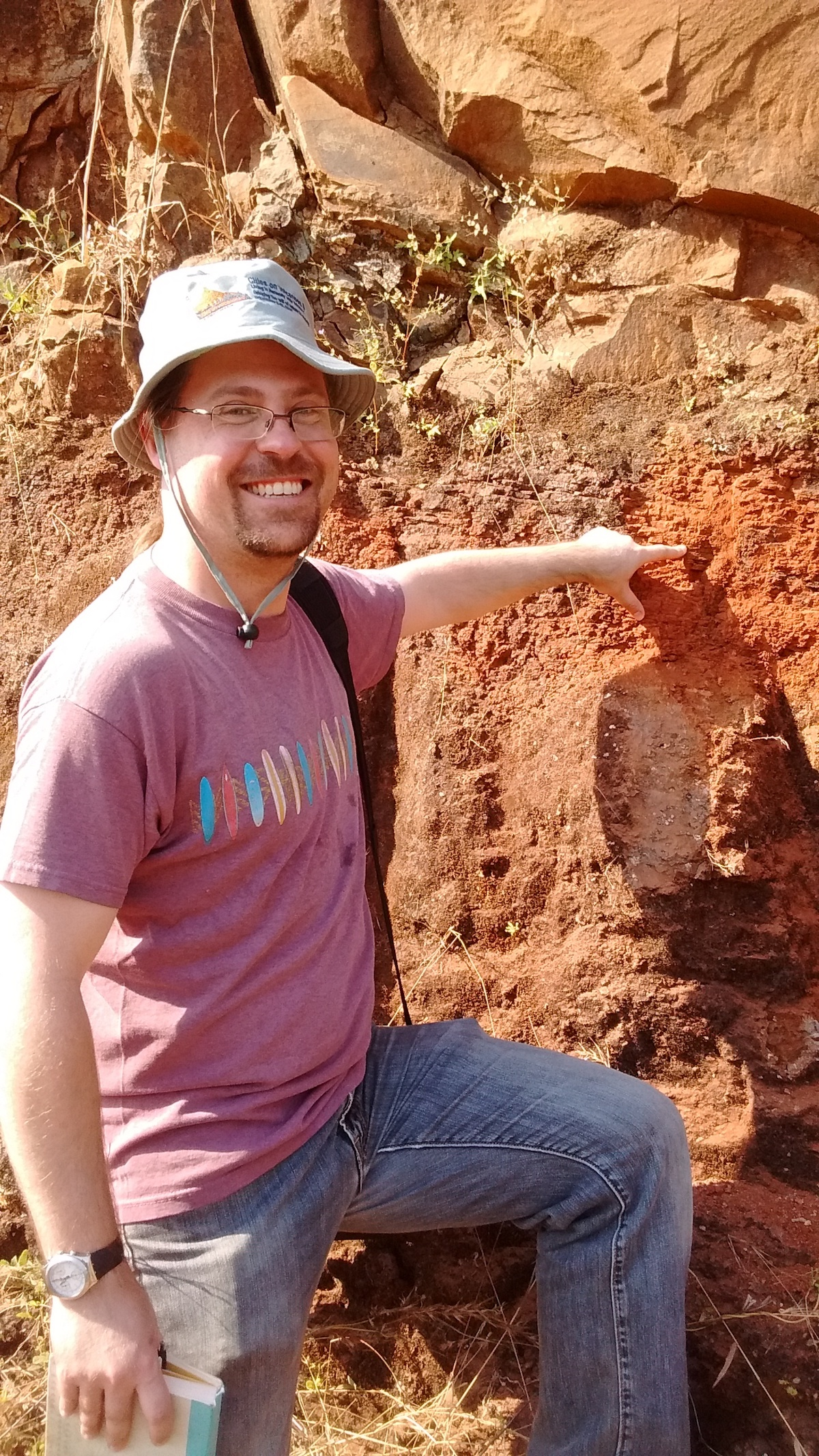 Vanderkluysen points at a red bole that marks the Bushe-Poladpur contact/Cretaceous-Paleogene boundary near the town of Poladpur in the Western Ghats. Image credit, Courtney Sprain.