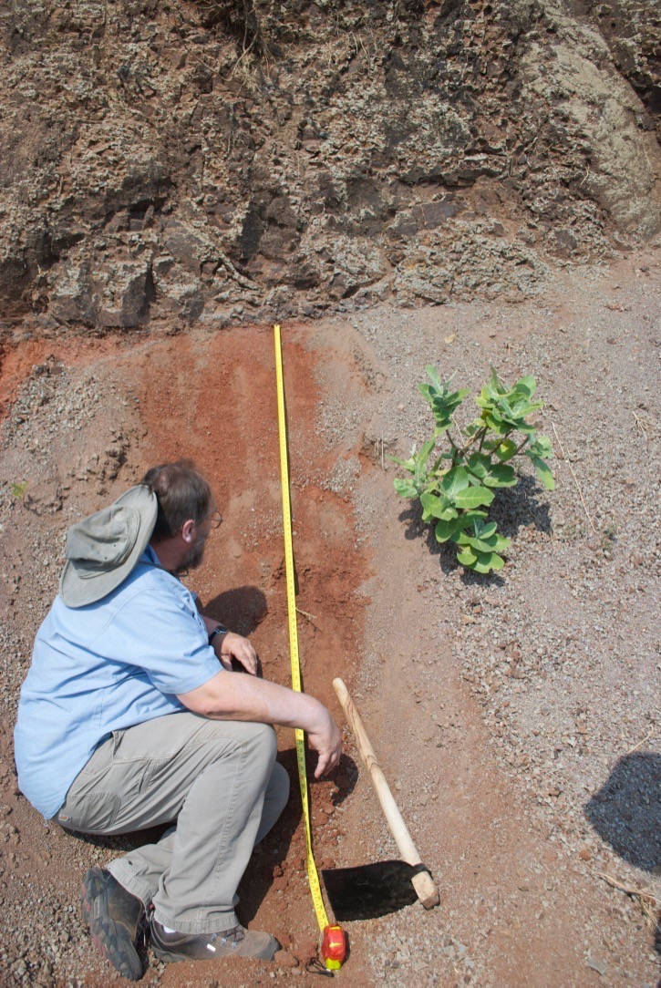 Prof. Paul Renne inspects profile of a red bole within the Ambenali Formation near the town of Mahabaleshwar. Image credit, Loÿc Vanderkluysen.