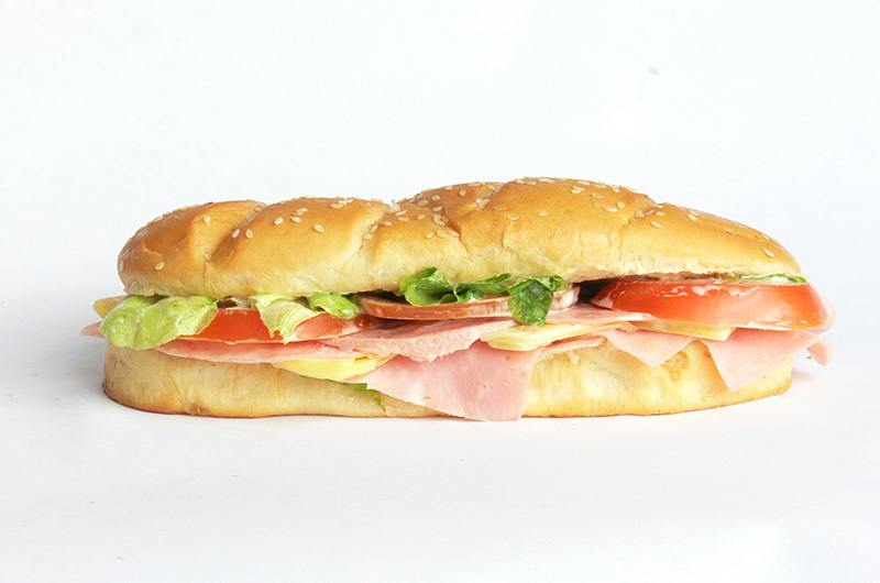 Hoagie with meat, cheese, lettuce and tomato.