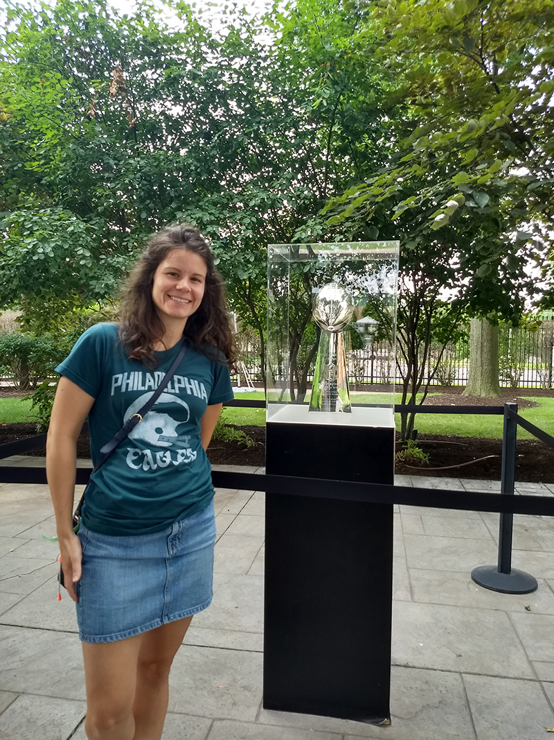 Jessica Rast, MPH '14, research associate in the A.J. Drexel Autism Institute, stands next to the Vince Lombardi trophy. She was a virtual participant in last year's Eagles Autism Challenge and will run in this year's event.