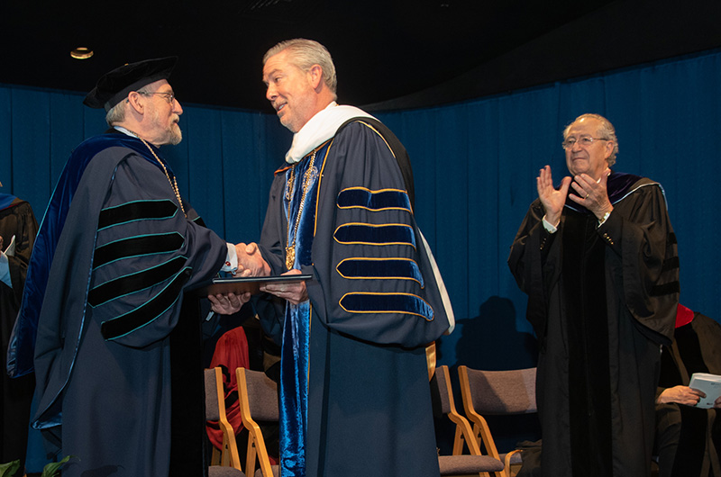 Gratz College President Paul Finkelman, PhD, shakes hands with Drexel University President John Fry as Gratz College Board of Governors member Leon L. Levy looks on.
