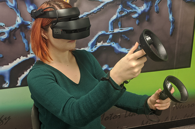 Woman wearing virtual reality headset and using handheld controllers.