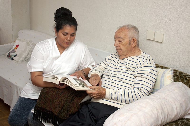 Nurse assisting elderly man with book