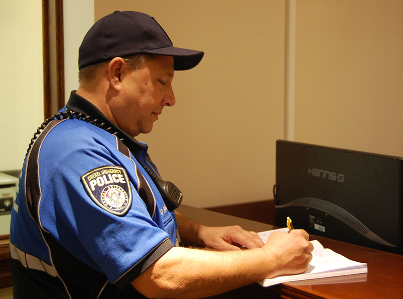 Officer Barone signs a logbook marking his patrol route throughout campus.