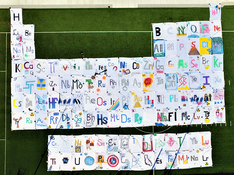 In celebration of both the International Year of the Periodic Table in 2019 and National Chemistry Week, students from two chemistry organizations unfurled a 100-foot-tall, 135-foot-wide handmade periodic table on Buckley Field.