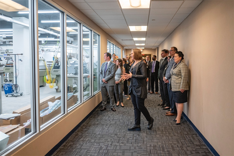 Director Geneviève Dion leads tour guests, including Neil Weaver (far left), Secretary of the Department of Community and Economic Development from the office of Governor Tom Wolf, as they view the manufacturing space for the first time before entering. The machinery/technology in the space was funded in part by a $1.5 million grant from the Commonwealth of Pennsylvania.