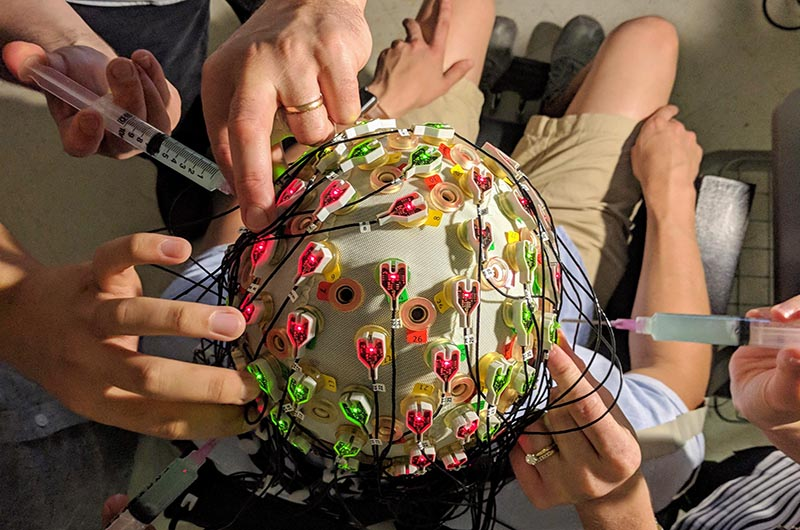 Researchers' hands preparing a test subject by dispensing conductive electrode gel into the electrodes in an EEG cap (top view of head).