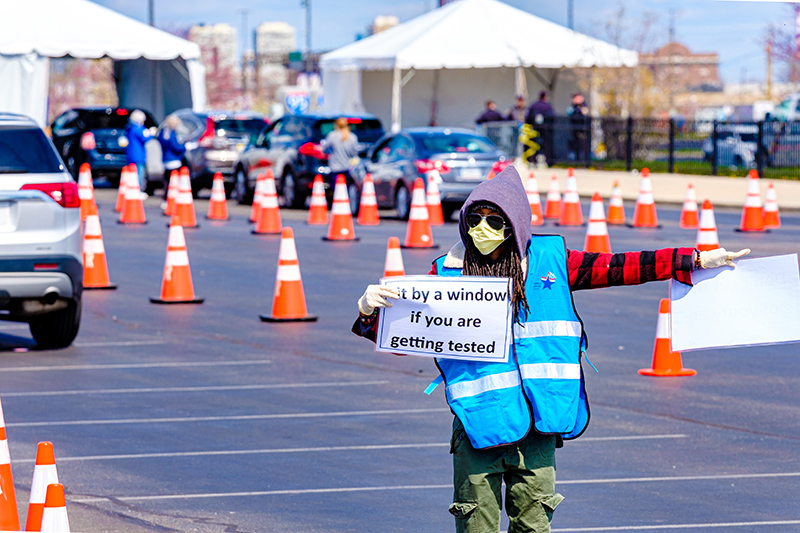 A volunteer directed traffic and used signs to help those wanting to take a coronavirus test.