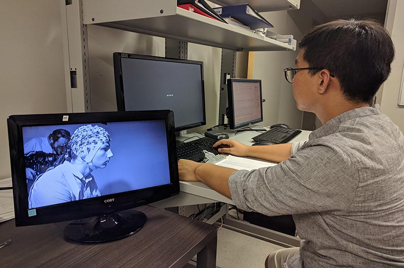 Research looking at monitor, running an EEG test session.