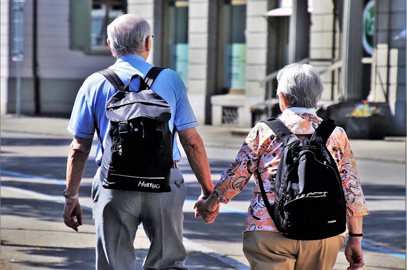 Older man and women holding hands and wearing backpacks.