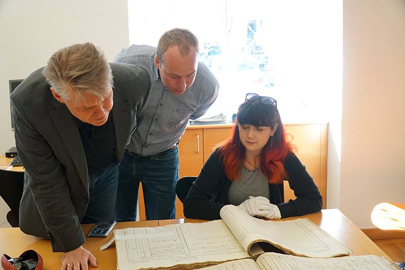 From left to right: Dornbirn archivists Werner Matt and Philipp Wittwer with Isabella Sangaline examining a primary source document at the Dornbirn City Archives during the 2018 Drexel trip to Dornbirn. Photo credit: Roxzine Scott.