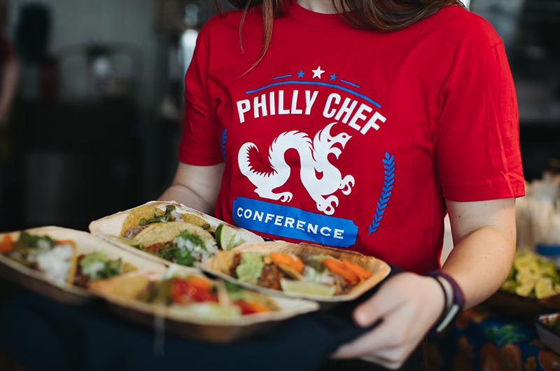 Person in a Philly Chef Conference t-shirt holding a tray of food