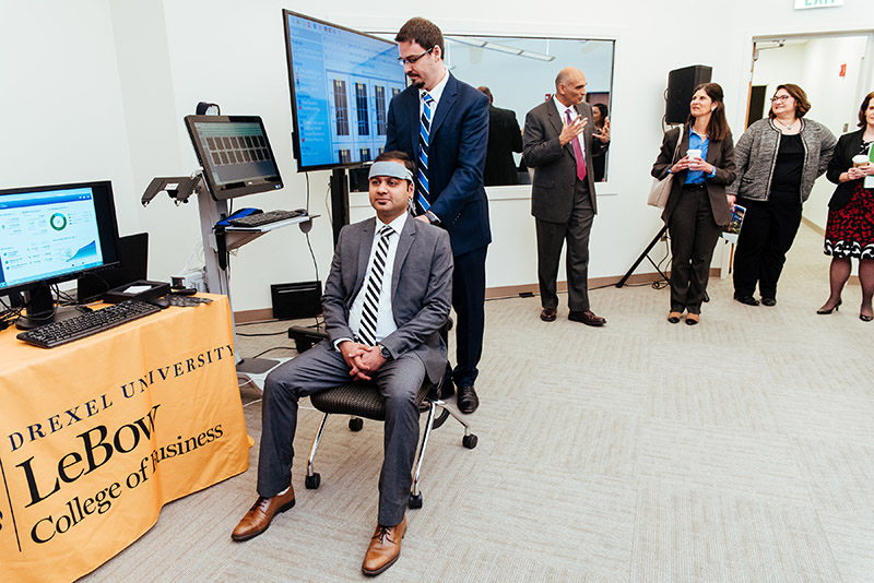 School of Biomedical Engineering, Science and Health Systems Associate Professor Hasan Ayaz, PhD, adjusted the fNIR device on then-PhD student Siddharth Bhatt, from the LeBow College of Business in this photo taken in the Behavior Lab at an event highlighting the successful partnership between SEI and Drexel University. Photo courtesy DSI.