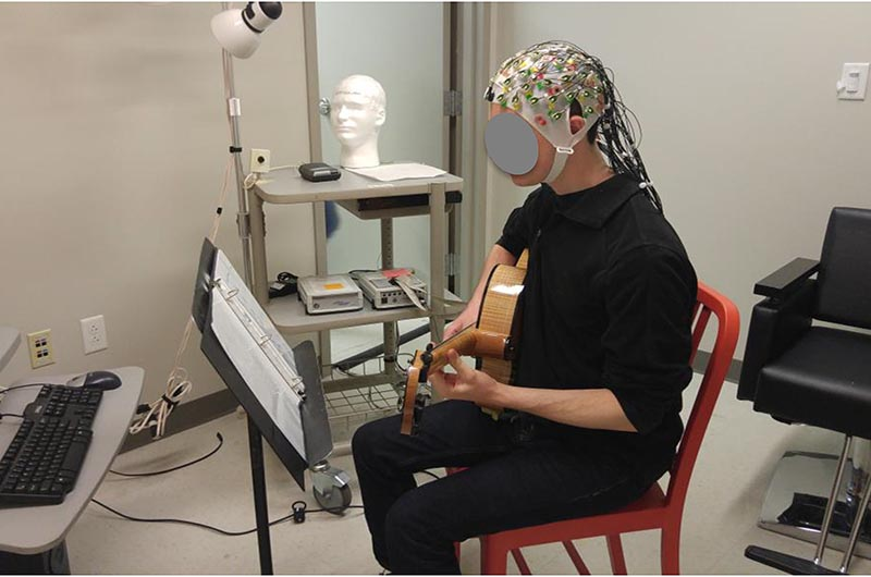 Unidentified male playing guitar while his brain activity is recorded.