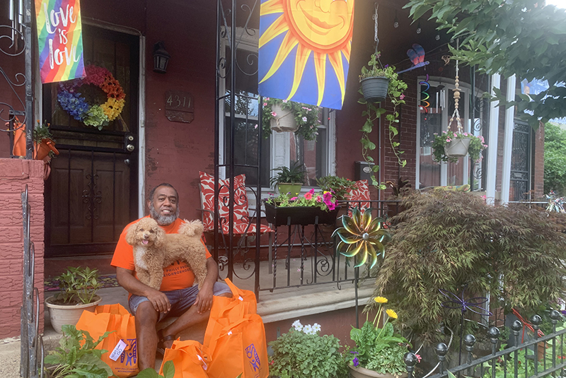 Jeffrey Jordan on his porch with his dog, Justice, surrounded by supplies to distribute to the West Philadelphia Promise Neighborhood. Photo courtesy Jeffrey Jordan.