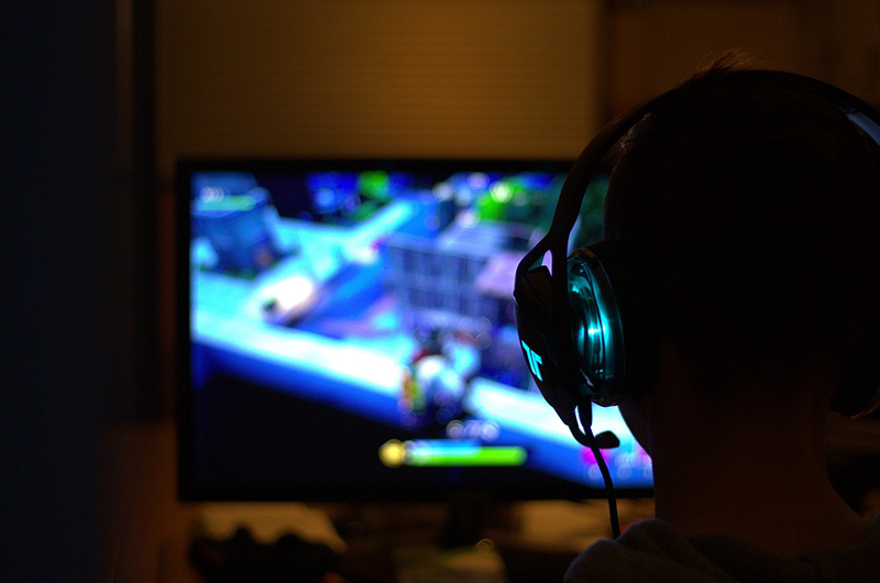 Silhouette of a person with headphones on in front a monitor playing a video game.